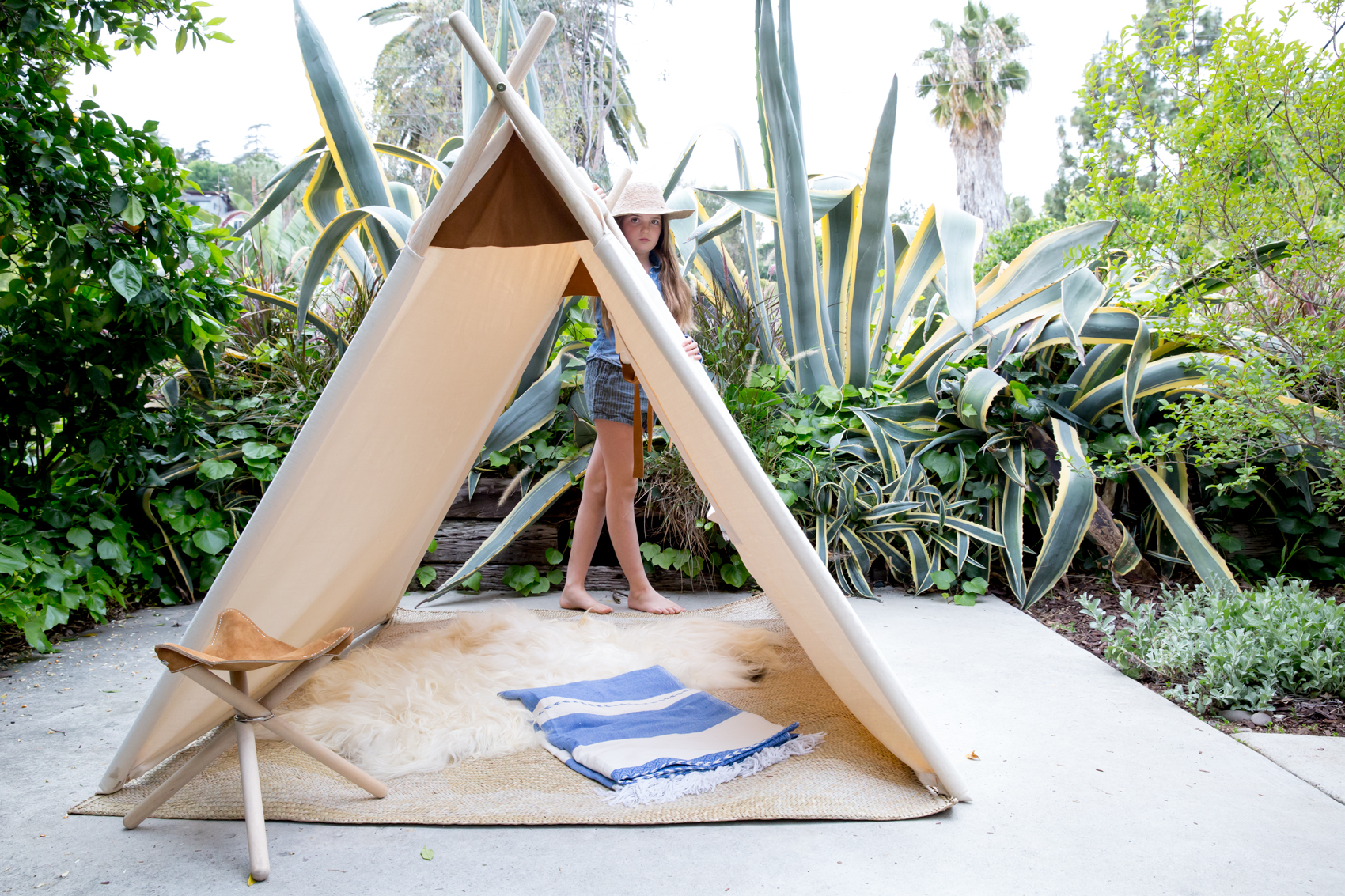 Field tent natural canvas teepee and backcountry stool with girl